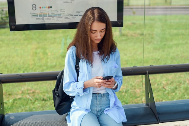 Очаровательная девушка с модным взглядом использовать смартфон во время ожидания на автобусной остановке. женщина держит мобильный телефон, сидя на общественной станции и ждет такси. Premium Фотографии
