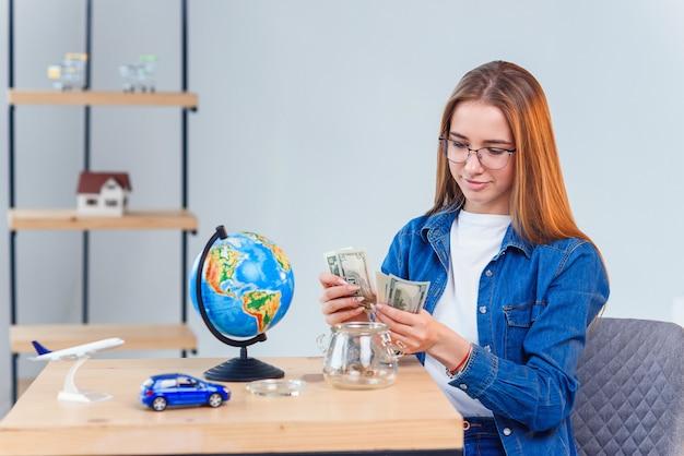 Молодая девушка считает деньги из копилки сидя за столом. понятие финансовой грамотности и сбережений. прозрачная копилка с банкнотами. Premium Фотографии