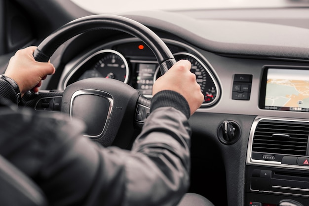 Бизнесмен за рулем роскошного современного автомобиля в городе. Premium Фотографии