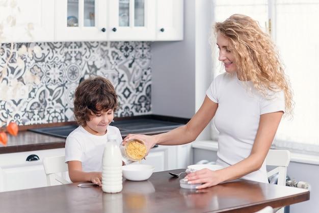 Красивая мама готовит здоровый завтрак из кукурузных хлопьев и молока для любимого сына. Premium Фотографии