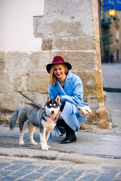 青いコートで幸せな笑顔と路上で若い犬犬種ハスキーとバーガンディの帽子を持つ若い幸せな観光女の子 Premium写真