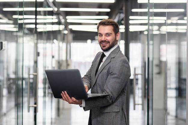 Усмехаясь бородатый бизнесмен сфокусировал на данных компании пока стоящ в коридоре офиса и использующ компьтер-книжку. Premium Фотографии