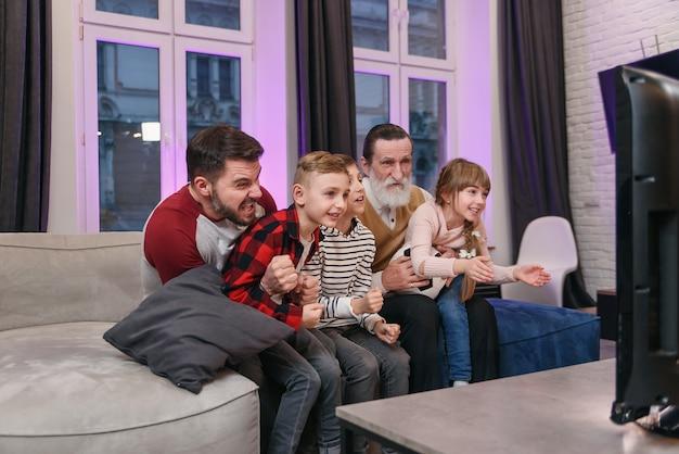 Привлекательные три поколения людей, таких как отец, дедушка и внуки, сидят дома на удобном диване и наслаждаются досугом, наблюдая за футбольным матчем, крича, когда команда забивает мяч. Premium Фотографии