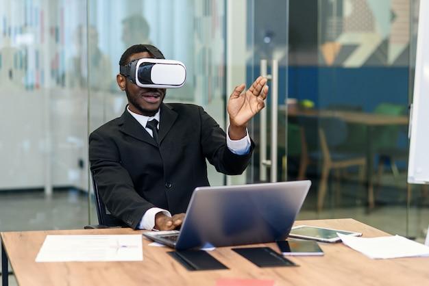 Портрет молодой афроамериканец черный мужской профессионал с использованием голографической голограммы дополненной реальности в современном офисе Premium Фотографии