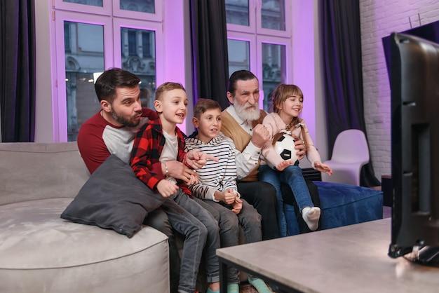 Взволнованные привлекательные три поколения людей, такие как папа, дедушка и внуки, которые все сидят дома на диване Premium Фотографии