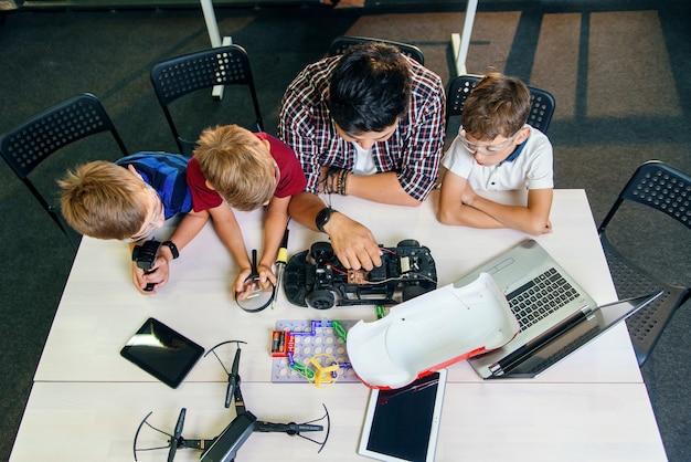 ラジコンカーモデルと一緒に働く若いヨーロッパの学生と電子工学教師。 Premium写真