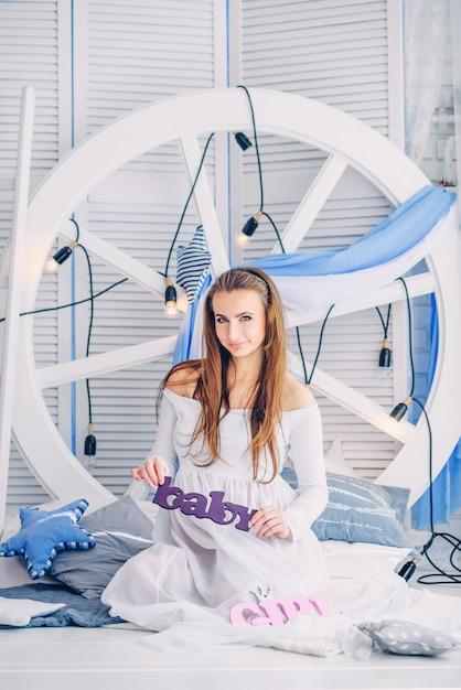白いドレスを着た美しい妊娠中の女性は、電球と木製のスクリーンと妊娠中の腹を保持している大きな白いホイールの背景にスタイリッシュなクッションの間に座っています Premium写真