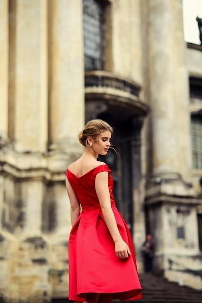 列を持つ歴史的な建物の近くに立っている赤いドレスの魅力的な美しい女性 Premium写真