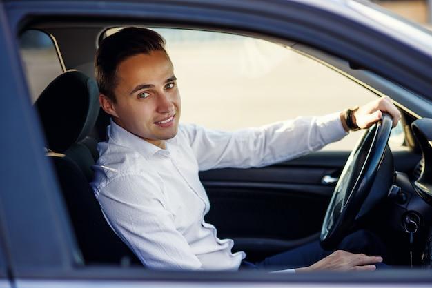高価な車を運転して白いシャツで魅力的なハンサムな笑みを浮かべて男 Premium写真