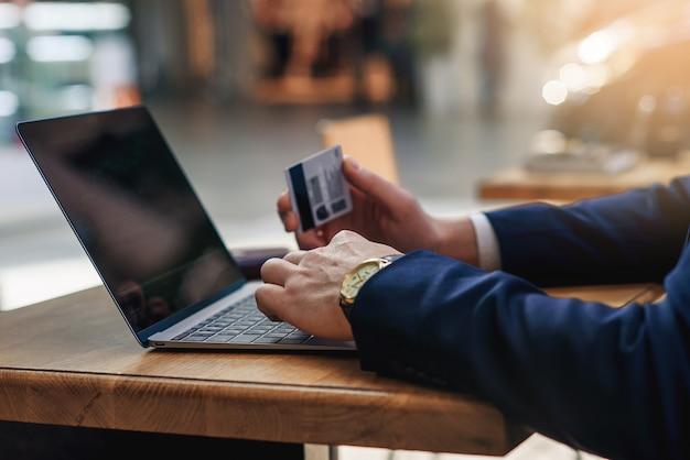 Бизнесмен держа номера кредитной карточки печатая на клавиатуре компьютера пока сидящ на кафе на деревянном столе Premium Фотографии