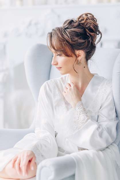 Портрет молодой красивой невесты в элегантном белом халате, сидя на стуле в ярком интерьере Premium Фотографии