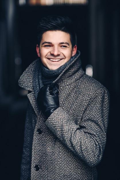 Красивый улыбающийся молодой человек в теплом пальто и кожаных перчатках Premium Фотографии