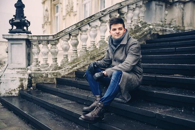 Молодой стильный мужчина в теплом сером пальто и кожаных перчатках сидит на лестнице Premium Фотографии