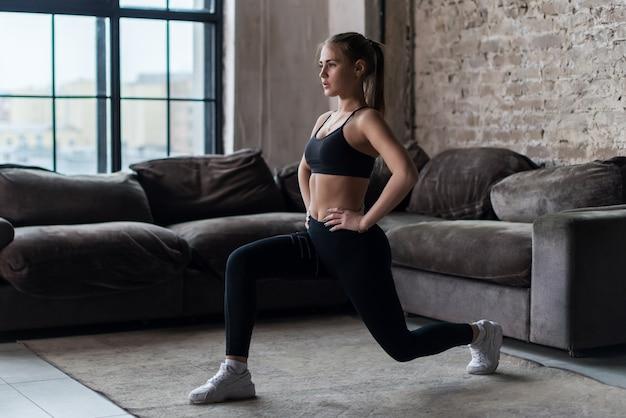 フラットで屋内で前頭突進またはスクワット運動を行うかなりフィット女性 Premium写真