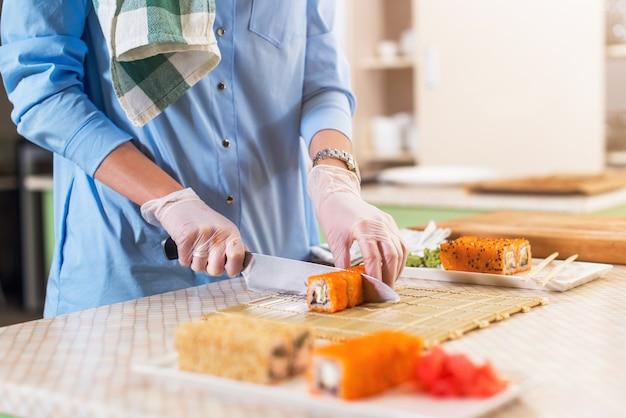 伝統的な日本の寿司を調理する手袋で女性の手のクローズアップロールキッチンでナイフで切断 Premium写真