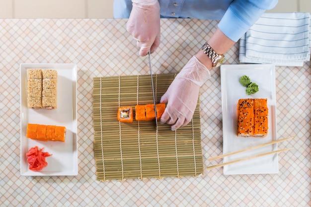 レストランで巻き寿司を作る手袋で働く女性シェフのトップビュー Premium写真