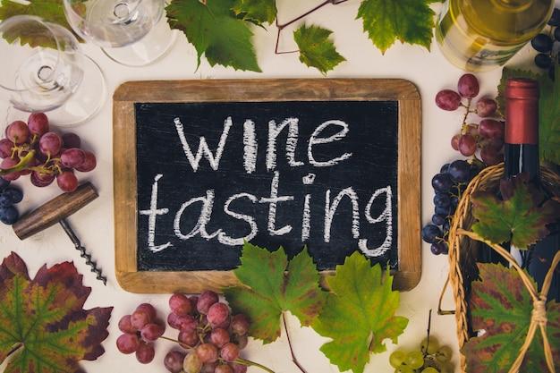 「ワインテイスティング」テキスト付きの黒板。ワイン、ブドウ、ブドウの葉のボトル。上面図 Premium写真