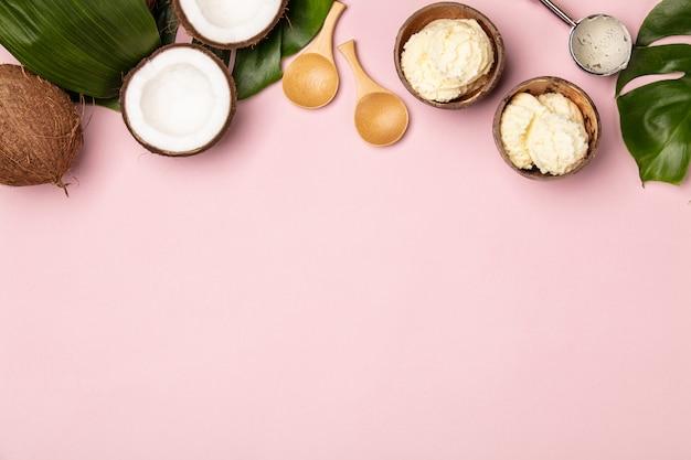Креативная плоская планировка с кокосовым мороженым и тропическими растениями на розовом фоне Premium Фотографии
