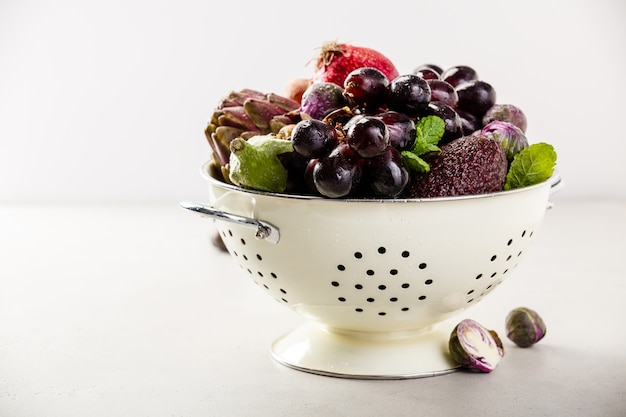 Фиолетовые фрукты и овощи в дуршлаге Premium Фотографии