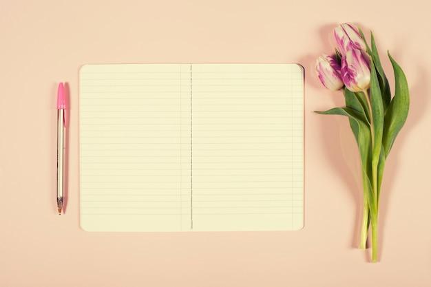 ピンクのチューリップの花束とノートブックを開く Premium写真