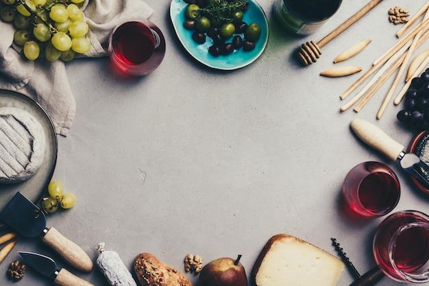 素朴なコンクリート背景に豚肉盛り合わせと赤ワイン Premium写真