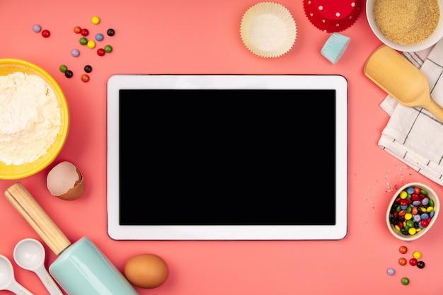 Выпечки ингредиенты с пустой планшет на розовом фоне, плоская планировка Premium Фотографии