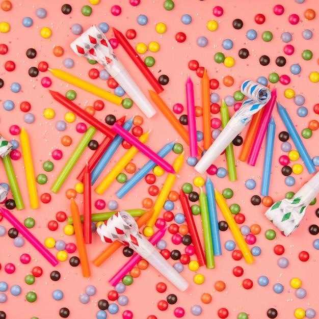 ピンクの背景にカラフルな振りかける、送風機、誕生日キャンドル Premium写真