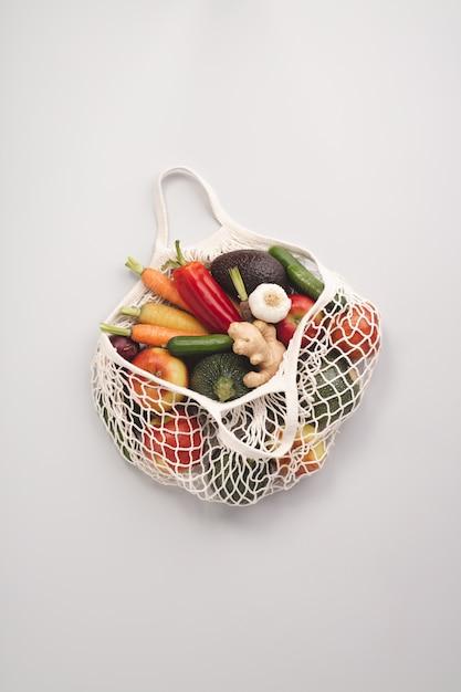 メッシュテキスタイルバッグの新鮮な有機果物と野菜 Premium写真