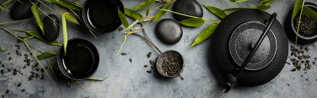 Бамбуковые ветви и зеленый чай на бетонном фоне Premium Фотографии