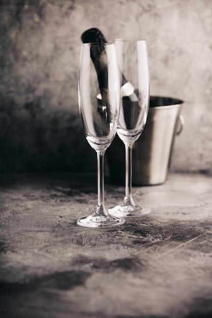 Бутылка шампанского в ведре со льдом и бокалами Premium Фотографии