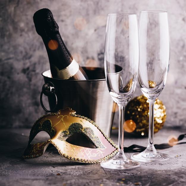 Бутылка шампанского в ведре со льдом, бокалы и рождественские украшения Premium Фотографии