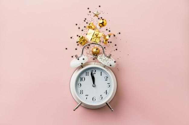 レトロな目覚まし時計とクリスマスの装飾とピンクの背景にクリスマスや新年の組成 Premium写真