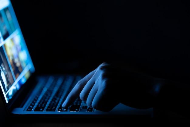 Рука человека, используя портативный компьютер в темноте Premium Фотографии