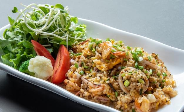 Вкусные жареные рисовые морепродукты на современной белой тарелке Premium Фотографии