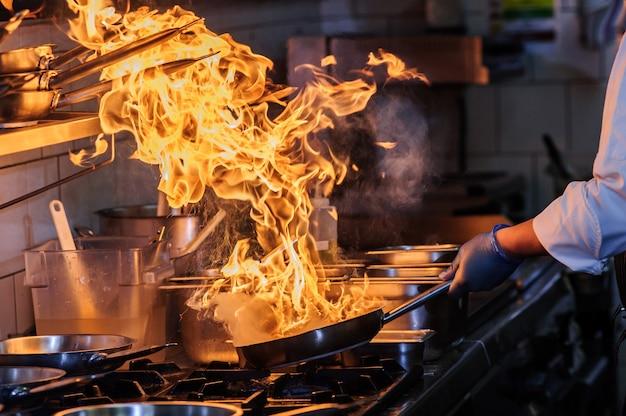 Шеф-повар готовит на кухне, в ресторане работает на огне, готовит крупный план, готовит жареные овощи на коммерческой кухне. китайский стиль сычуаньской кухни. Premium Фотографии