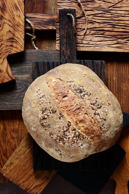 Свежий хрустящий французский домашний хлеб на деревянных досках. хлеб на закваске. пресный Premium Фотографии