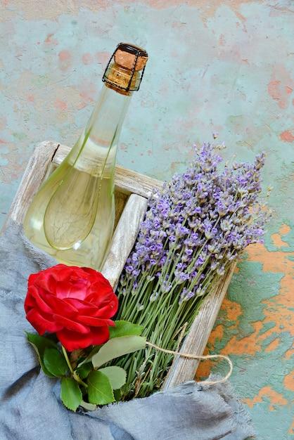 Деревянная коробка с бутылкой охлажденного шампанского и букетом лаванды Premium Фотографии