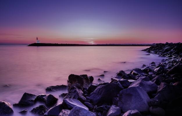 海岸のロングショットで壮大な夕日 無料写真