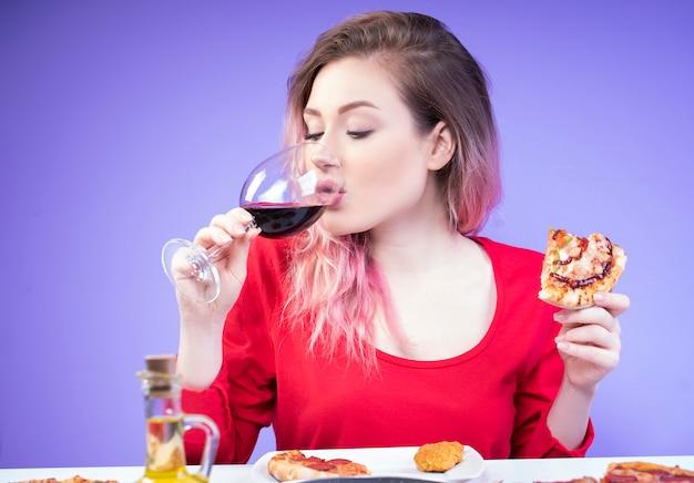 Красивая женщина пьет вино и держит в руке кусок пиццы Бесплатные Фотографии