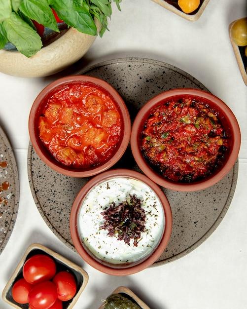 テーブルの上のさまざまな料理とトマトのトレイ 無料写真