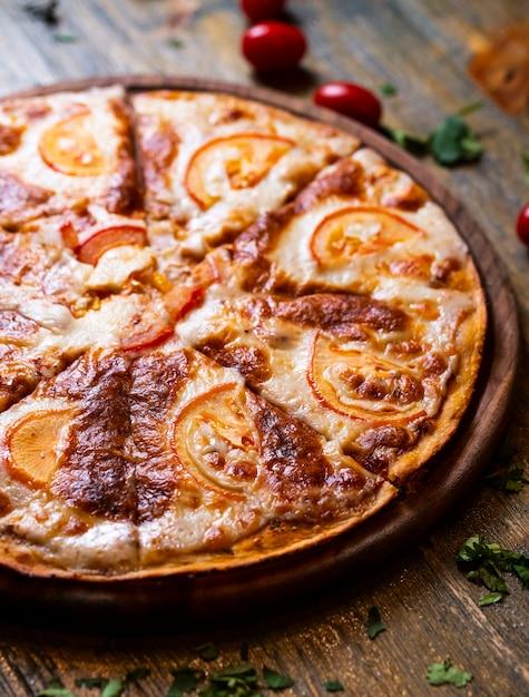 木製の机の上のトマトのピザ 無料写真