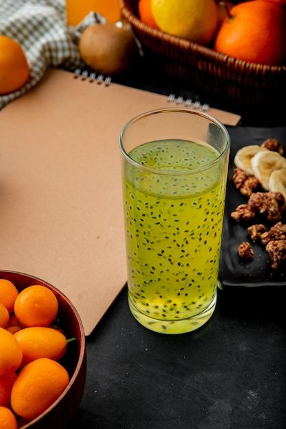 コピースペースと黒い表面にキンカンと他の果物とキウイジュース 無料写真
