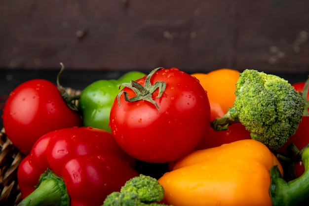 Вид сбоку овощей, как помидоры перцы брокколи на поверхности темно-бордовый Бесплатные Фотографии