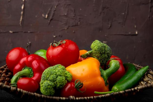 黒の表面とあずき色の表面にピーマンブロッコリーとトマトとして野菜がいっぱい入ったバスケットプレートの側面図 無料写真