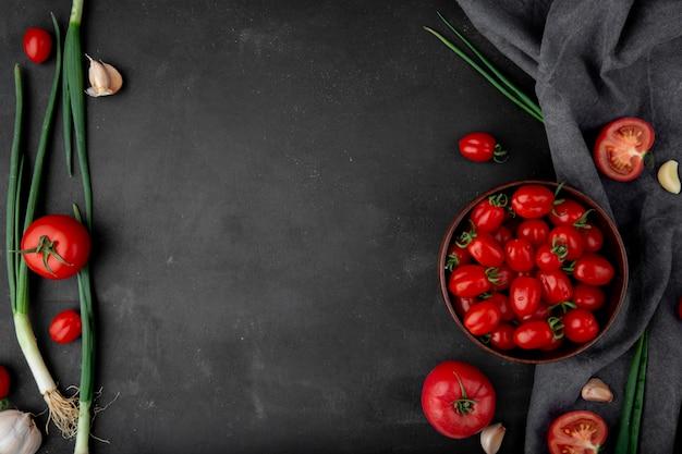 黒の表面にネギトマトとニンニクとして野菜のトップビュー 無料写真
