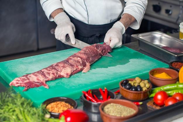 シェフがキッチンで真ん中から生の牛肉ステーキを切る 無料写真