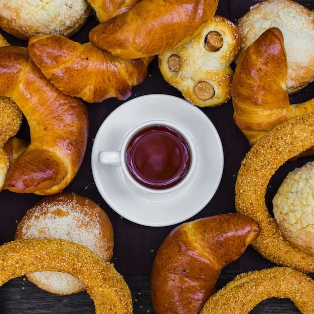 ホットドッグ、シミット、パンに囲まれた紅茶カップのトップビュー 無料写真
