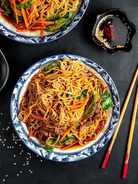 黒いテーブルで野菜と牛肉の麺 無料写真