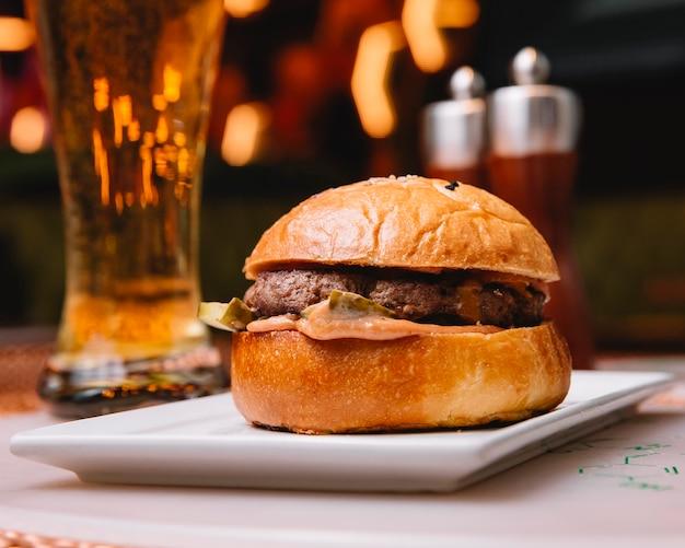 キュウリのピクルス添えビーフハンバーガーとビールのレストランでお召し上がりいただけます 無料写真