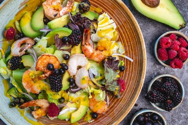 Сверху близкий вид салата здоровой диеты с жареными креветками, авокадо, красным луком и ягодами Бесплатные Фотографии